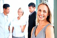 Portrait of a smiling casual businesswoman standing with her business colleagues behind