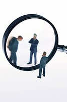 symbol picture ´headhunter´: three toy figures of business men, one watching the others throug a magnifying glass