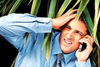 Tensed businessman hiding under foliage while on cell phone