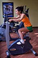 young woman in a fitness studion sitting on an exercise bicycle with a smile