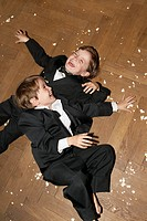 Two boys lying on floor playing with popcorn