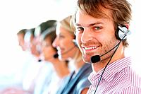 Closeup of smiling call center executive with his team in blur background