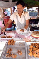 woman saling crumbed meat delicacies at a market stand, Thailand, Krabi