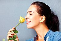 Side view of pretty woman smelling yellow rose