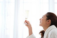 Young Woman in Dressing Gown Having Champagne