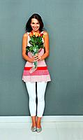 Full length of attractive young woman holding bunch of fresh flowers