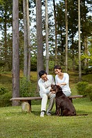 Couple with Chocolate Labrador in Park
