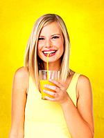 Attractive woman sipping orange juice against yellow background