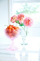 Cherries in a glass and roses in vase