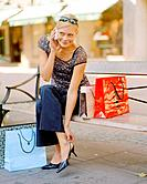 Young blond woman with shopping bags sitting on bench, full_lenght portrait