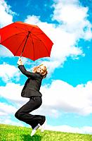 Portrait of business woman jumping in joy with umbrella