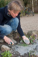 woman intermixing rock meal with the soil of a flower bed in order to improve its quality, Germany