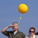 two persons on the viewing platform of coal mine Zollverein watching the big yellow balloons over European Capital of Culture Essen marking former sit...
