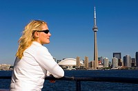 Young woman looks across lake Ontario to downtown from Islands ferry boat, Toronto, Ontario, Canada.