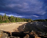 Boreal forest and driftwood along the shoreline at North Beach in Pukaskwa National Park, Ontario, Canada.
