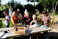 primary school pupils watching animals in an aquarium and under a microscope caught in the self_built pond in the school garden