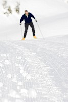 Detail of a groomed cross country ski trail with a male skier in the background. Strathcona Provincial Park, British Columbia, Canada.