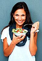 Woman smiling while holding a bowl of salad against blue background