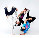 Portrait of a young bboying group performing dance moves against grey background