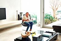Portrait of a woman sitting in chair at beautiful living room in modern home