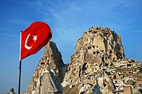 historical cave architecture built into tuff formations with the turkish flag waving in the foreground, Turkey, Cappadocia, Uchisar