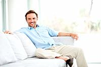 Portrait of an attractive young man sitting comfortably on couch and smiling _ Indoor