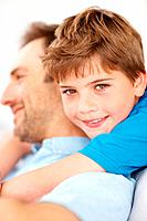 Closeup portrait of a happy young child hugging his father from behind _ Indoor