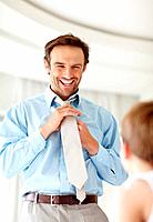 Portrait of a happy young father wearing tie with his son standing in front