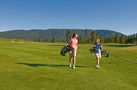 A young women and her junior golfer companion enjoy a beautiful day while walking down a fairway, on Two Eagles Golf Course in Westbank, British Colum...