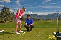 A woman gets lessons from the head pro at Two Eagles Golf Course in Westbank, British Columbia, Canada