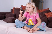 girl with MP3_Player sitting on a bed