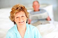 Portrait of a beautiful senior female with a blurred man reading newspaper on background