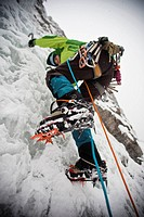 A female ice climber setting her crampons as she climbs some steep ice. Moonlight WI4, Even Thomas Creek, Kananaskis, Alberta, Canada
