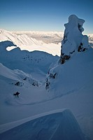 A male splitboarder drops into a couloir in the Kicking Horse Backcountry, Britsh Columbia, Canada
