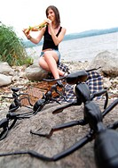 ants on a rock watching a young woman at a lake shore eating a baguette