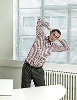 Man Stretching in Office
