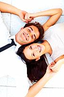 Closeup of beautiful young business couple lying on floor holding hands and smiling