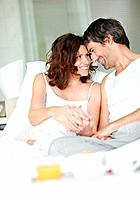 Portrait of relaxed mature couple lying on bed smiling