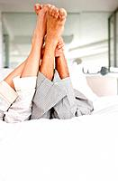 Legs of love couple lying on bed at home _ Indoor
