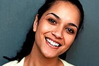 Closeup portrait of a happy young Indian woman smiling against grey background