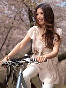 Young smiling Asian woman riding a bicycle in a park past blooming cherry trees