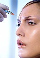 Young Woman´s Face Getting Botox Syringe in Forehead