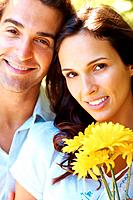 Closeup portrait of beautiful young love couple with yellow flowers