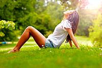 Relaxed young girl sitting on grass in park _ Outdoor