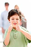 Portrait of sweet boy showing thumbs up with his parents in background _ Outdoors
