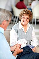 Senior couple enjoying playing cards together at a club