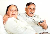 Closeup portrait of a handsome senior man watching televison with his wife
