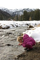girl in winter drinking clear water from a cold mountain creek