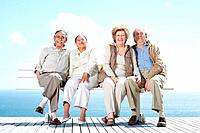 Portrait of a happy senior couples sitting together on the bench against the sky _ Outdoor