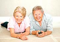 Portrait of a sweet senior couple watching television while lying down on the floor
